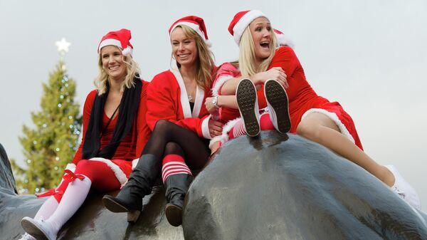 Девушки в костюмах Санта-Клауса на Трафальгарской площади в центре Лондона