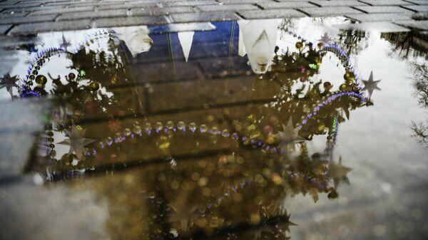 Отражение в луже новогодней елки, установленной на Тверской улице