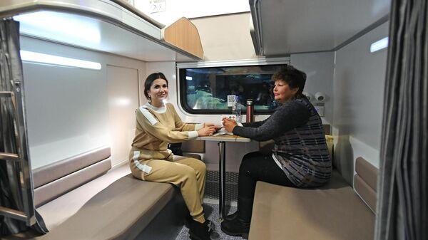 Пассажиры в павильоне с макетом нового плацкартного вагона, представленном в зале ожидания Казанского вокзала в Москве