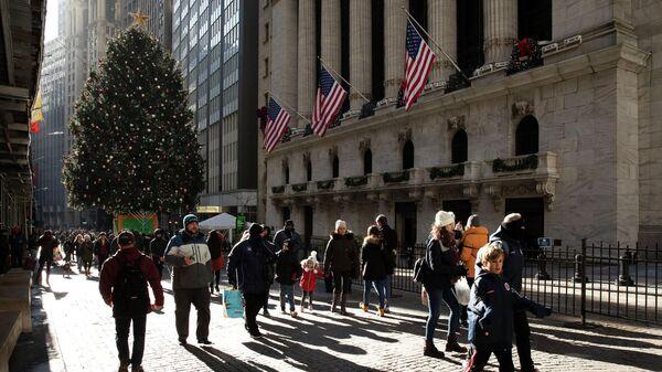 Люди проходят мимо Нью-Йоркской фондовой биржи