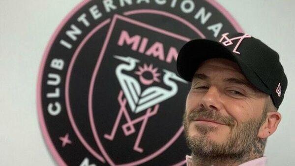 Дэвид Бекхэм на фоне эмблемы футбольного клуба Интер Майами.