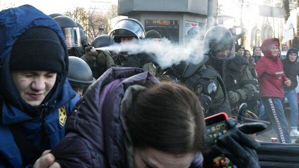 Сотрудники полиции используют слезоточивый газ против участников акции протеста против земельной реформы возле здания Верховной рады в Киеве. 17 декабря 2019