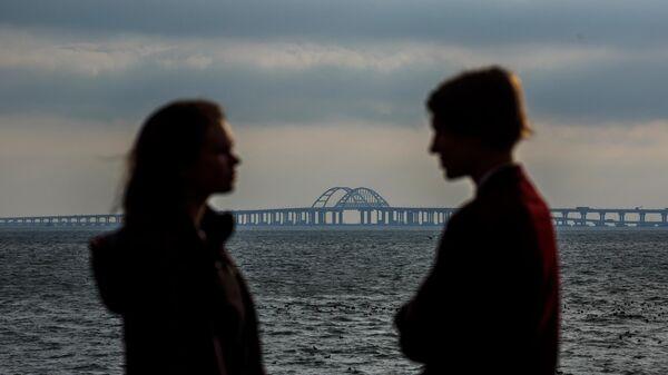 Молодые люди стоят напротив Крымского моста