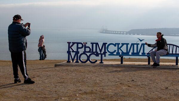 Люди фотографируются напротив Крымского моста