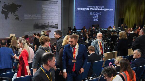 Журналисты с плакатами перед началом ежегодной большой пресс-конференции президента РФ Владимира Путина