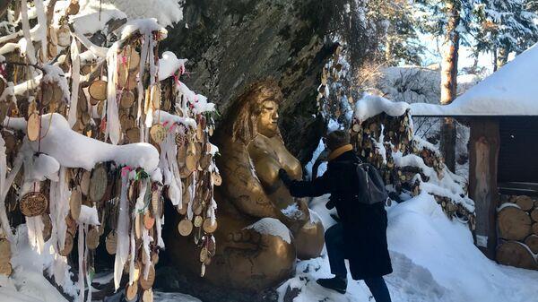 Туристка загадывает желание около Золотой бабы на горе Малая Синюха