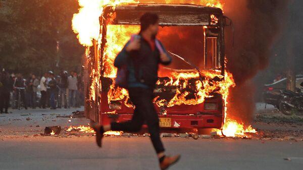 Мужчина пробегает мимо горящего автобуса, который был подожжен демонстрантами во время протеста против нового закона в Нью-Дели, Индия. 15 декабря 2019 года