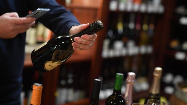 Сомелье фотографирует на смартфон бутылку с российским игристым вином