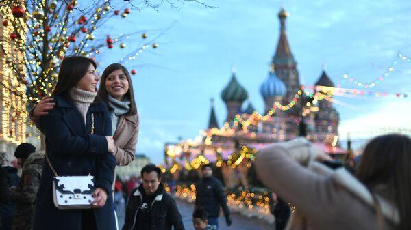 Девушки фотографируются на Красной площади в Москве