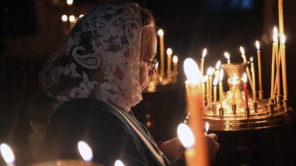 Верующая на Рождественском богослужении в Свято-Троицкой церкви города Томска