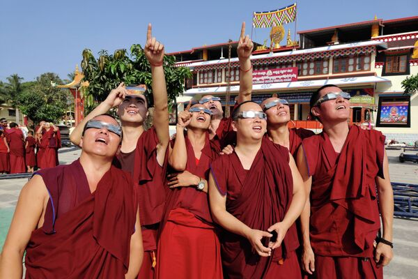 Монахи наблюдают солнечное затмение  в монастыре Гаден, в тибетской колонии Тегинкоппа, в Индии. 26 декабря 2019 года