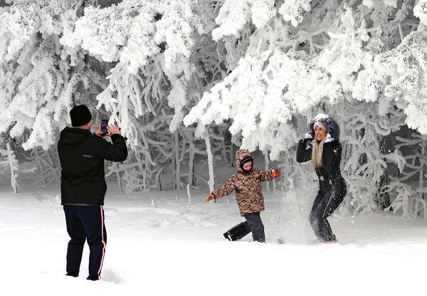 Люди фотографируются в заснеженном лесу на берегу реки Енисей