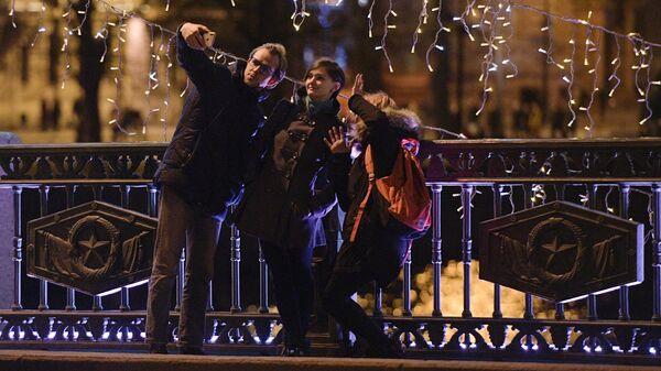 Люди фотографируются на Дворцовом мосту в Санкт-Петербурге в новогоднюю ночь