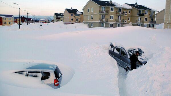 Житель села Троицкое Анивского района Сахалинской области откапывает свой автомобиль от снега