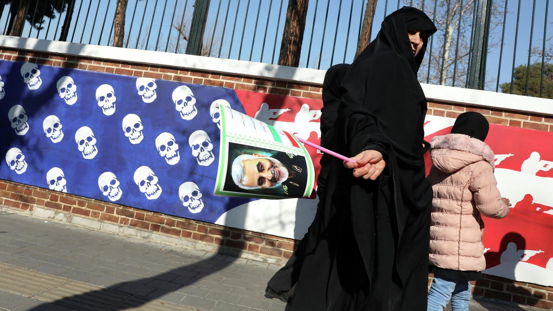 Женщина возвращается с похорон генерала Касема Сулеймани мимо посольства США в Тегеране  - РИА Новости, 1920, 28.12.2020