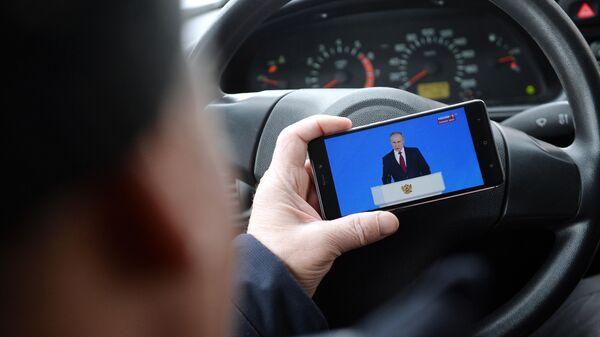 Житель Екатеринбурга смотрит трансляцию ежегодного послания президента РФ Владимира Путина Федеральному Собранию
