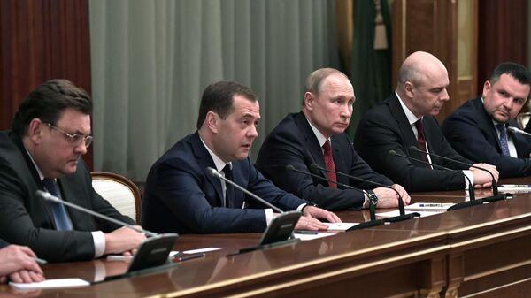Президент РФ Владимир Путин и председатель правительства РФ Дмитрий Медведев во время встречи с членами правительства России