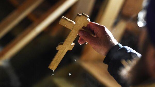 Священнослужитель совершает обряд освящения воды в праздник Крещения во Владивостоке