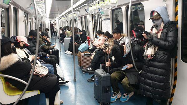 Пассажиры в защитных масках в вагоне метро в Пекине