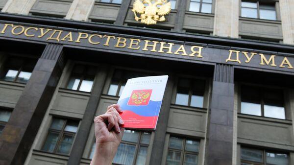 Конституция Российской Федерации на фоне здания Государственной Думы РФ