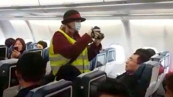 Сотрудник санитарно-карантинного пункта проводит дистанционную термометрию пассажиров на борту самолета, прибывшего в аэропорт Внуково