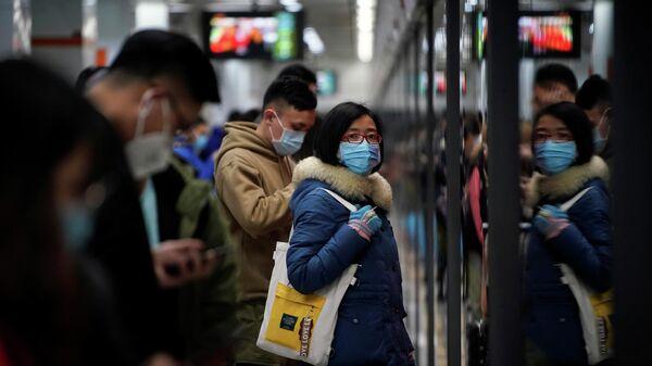 Люди в защитных масках в метро в Шанхае