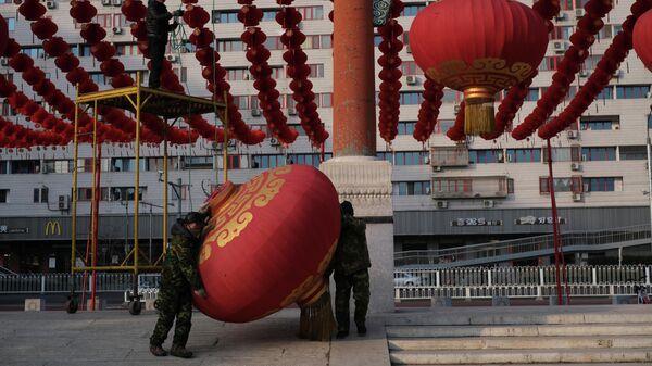 Рабочие демонтируют украшения в Пекине