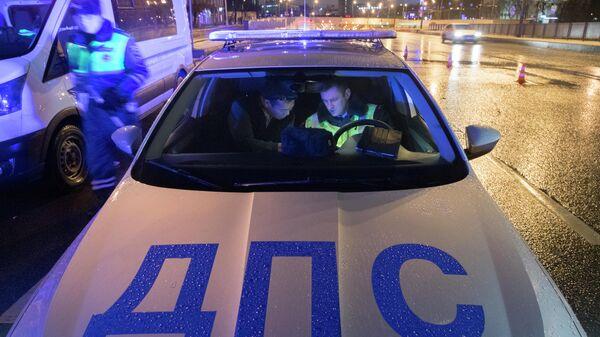 Сотрудник ДПС ГИБДД проводит проверку документов у водителя  в Москве
