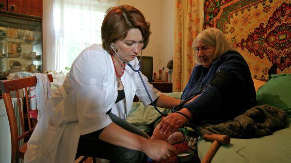 Врач измеряет артериальное давление пациентке во время выездного обслуживания