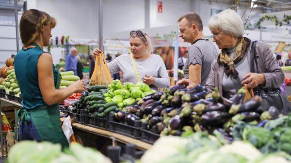 Посетители у прилавка с овощами на агропромышленной выставке