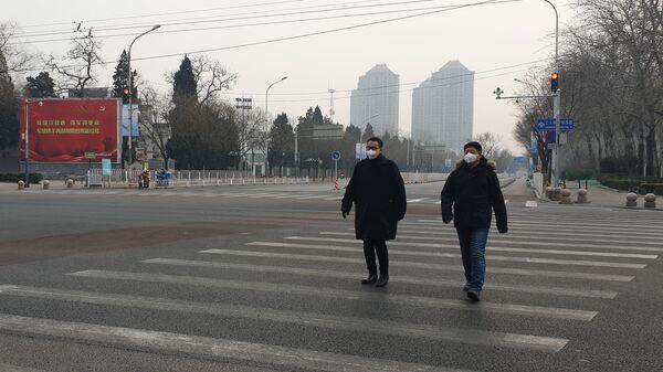 Мужчины в медицинских масках переходят улицу в Пекине