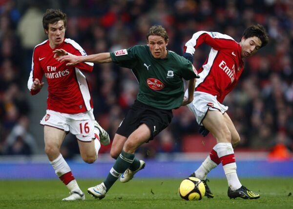 Форварды Арсенала Аарон Рамси (слева) и Самир Насри (справа) против футболиста Плимута Криса Кларка во время матча Кубка Англии