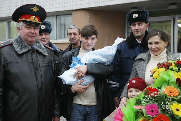 Сотрудники ГИБДД, принявшие роды на МКАД, с новорожденным и его родителями у роддома