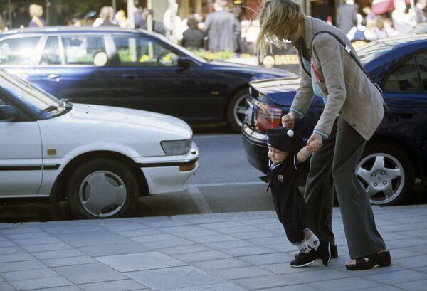 Молодая женщина с ребенком на городской улице. Архив
