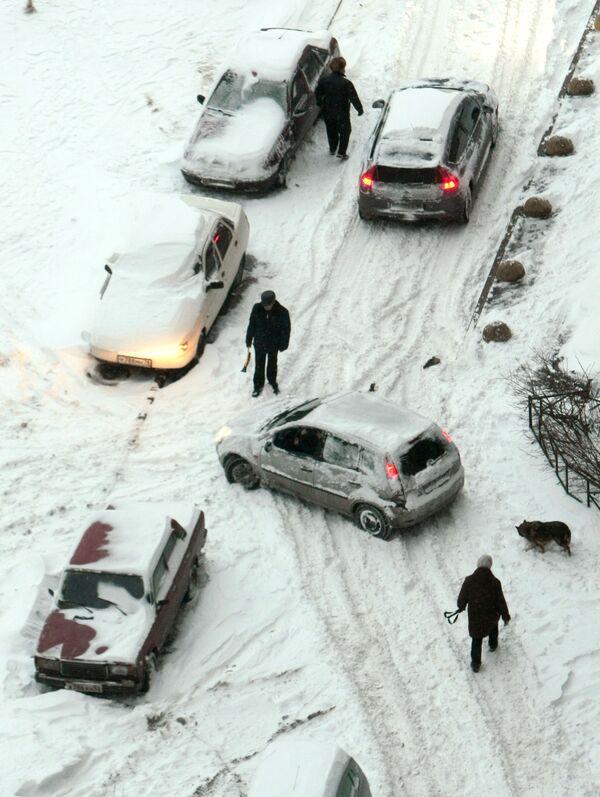 Автомобили и пешеходы на заснеженной улице. Архив