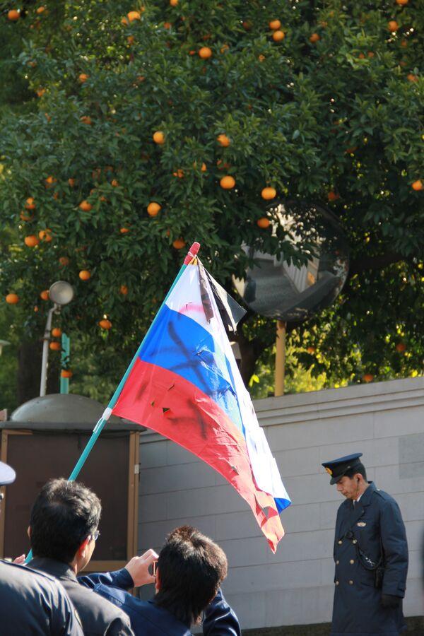Оскверненный российский флаг в руках у представителя ультраправой организации в Японии