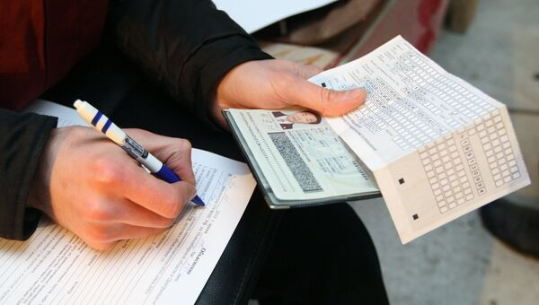 Сотрудник федеральной миграционной службы Новосибирской области проводит проверку документов у иностранных рабочих. Архивное фото