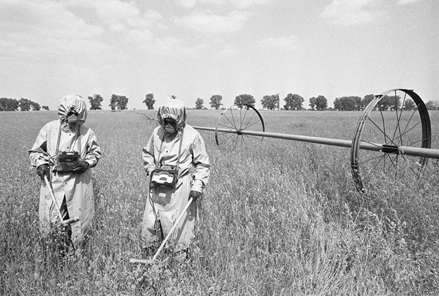 Дозиметристы в специальных костюмах проводят контроль радиации на полях в районе аварии на Чернобыльской АЭС