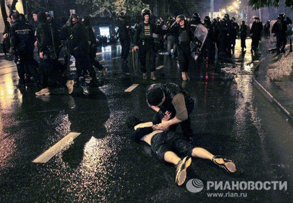 Полицейский задерживает участника акции протеста грузинской оппозиции во время беспорядков на проспекте Руставели в Тбилиси