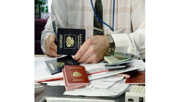 Сотрудник посольства проверяет паспорта. Архив