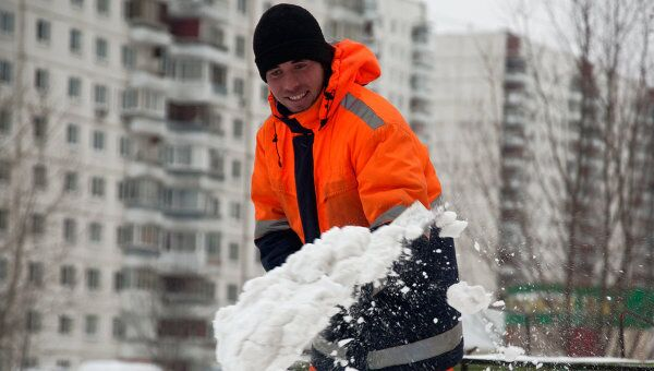 Дворник расчищает снег