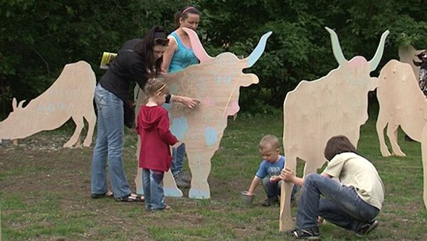 Дети раскрашивают фанерных коров на Зеленой неделе в парке Горького