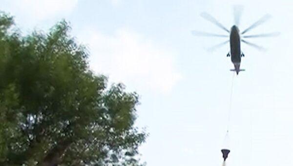 Вертолеты сбрасывают воду на горящий ангар в Москве