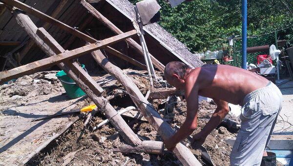 Житель хутора Верхнеадагум Виталий Торопков разбирает развалины своего дома