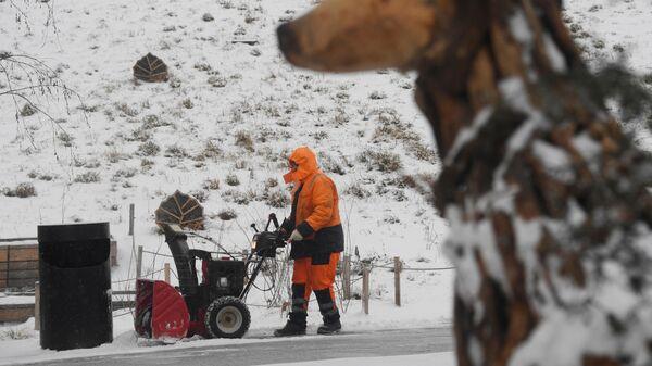 Сотрудник коммунальной службы убирает снег на территории природно-ландшафтного парка Зарядье в Москве