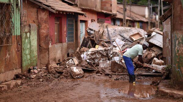 Житель расчищает завал возле своего дома после переполнения ручья Да Прата из-за проливных дождей в Бразилии. 28 января 2020