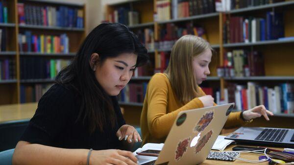 Девушки работают за компьютером в библиотеке