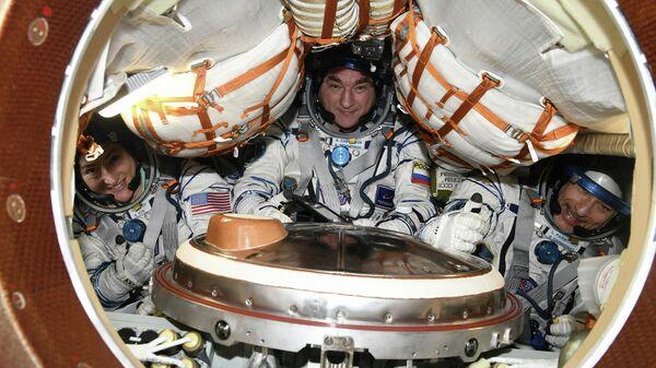 Космонавт Александр Скворцов и астронавты Лука Пармитано и Кристина Кук во время тренировки по спуску на корабле Союз МС-13