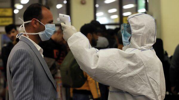 Медицинский работник проводит осмотр пассажира в аэропорту Басры, Ирак