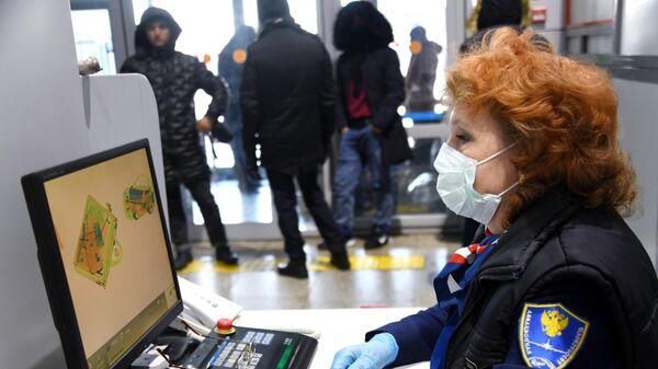Сотрудница авиационной службы безопасности осматривает багаж в аэропорту Кадала